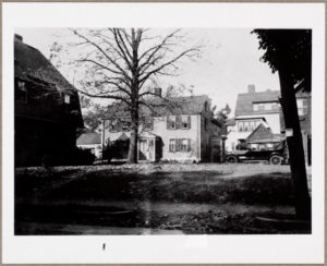 The Jason Russell House, hemmed-in by newer buildings on its historic battlefield and looking rather the worse for wear, as it appeared in the early 1920s prior to its purchase by the Arlington Historical Society.